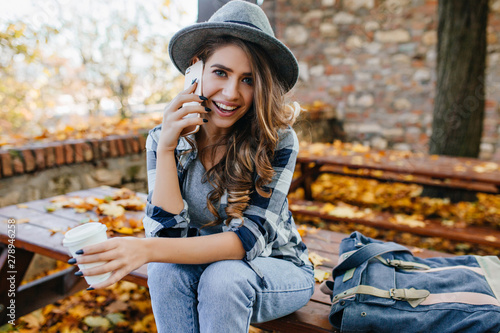 Fototapety, obrazy: Stunning blue-eyed lady with curly hairstyle calling friend in good autumn day. Cute european girl in casual jeans talking on phone on autumn background.