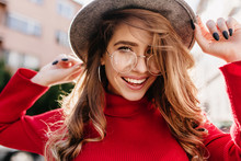 Gorgeous Young Woman With Sincere Smile Posing In Glasses In Sunny Autumn Day. Close-up Portrait Of Fascinating Lady With Black Nails Wears Red Knitted Clothes.
