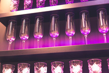 Shelf With A Lot Of Empty Wine Glasses With Pink And Violet Light. Bar Or Glassware Shop Interior. Celebration, Event Or Party Concept.