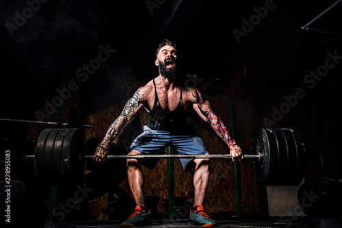 Fotografiet  Muscular fitness man doing deadlift of a barbell in modern fitness center