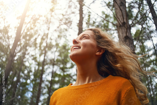 Fotomural  Blonde young woman looking up in the forest