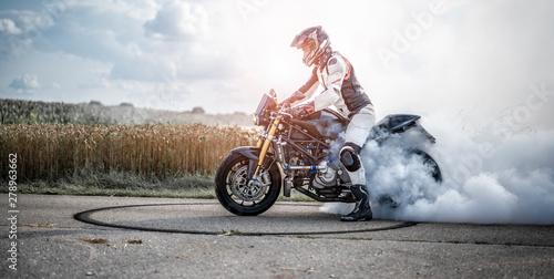 Vászonkép  wilder Motorradfahrer lässt die Reifen bei einem Burnout durchdrehen und macht e