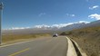 Local people driving across the breathtaking plains of the Himalayan Plateau. White SUV drives down an empty asphalt road and away from the snowy mountains in Tibet. Tourists on road trip across Tibet
