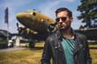 canvas print picture - Mann mit Sonnenbrille vor altem Flugzeug