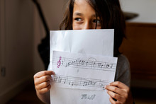 Close Up Of Boy Holding Composition Music Sheet