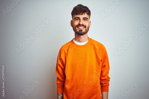 Young man with tattoo wearing orange sweater standing over isolated white background with a happy and cool smile on face Wallpaper Mural