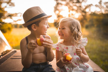 Two Young Children Eating Peaches On An Old Truck Summer Time Happy