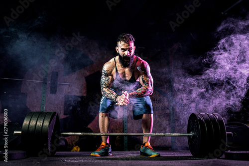 Photographie  Muscular fitness man preparing to deadlift a barbell in modern fitness center