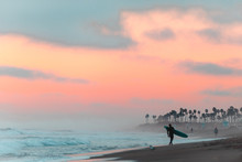 Man Walks On Beach With Surfboard At Sunrise