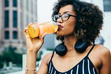 Young Woman Drinking Orange Ju...