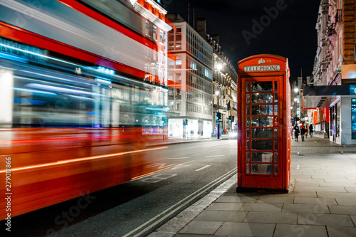 Poster Londres bus rouge Light trails of a double decker bus next to the iconic telephone booth in London