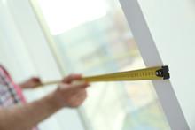 Man Measuring Window, Closeup View. Construction Tool