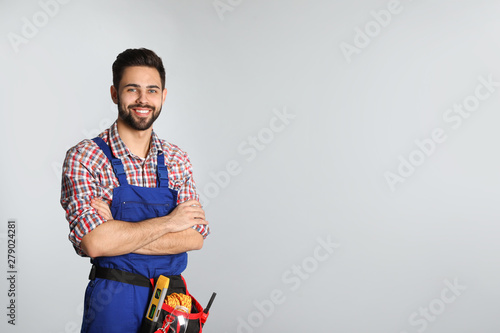 Obraz Portrait of construction worker with tool belt on light background. Space for text - fototapety do salonu