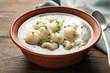 Leinwandbild Motiv Bowl of tasty dumplings in broth on wooden table