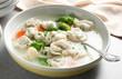 Leinwandbild Motiv Bowl of tasty dumplings in broth with spoon on table, closeup