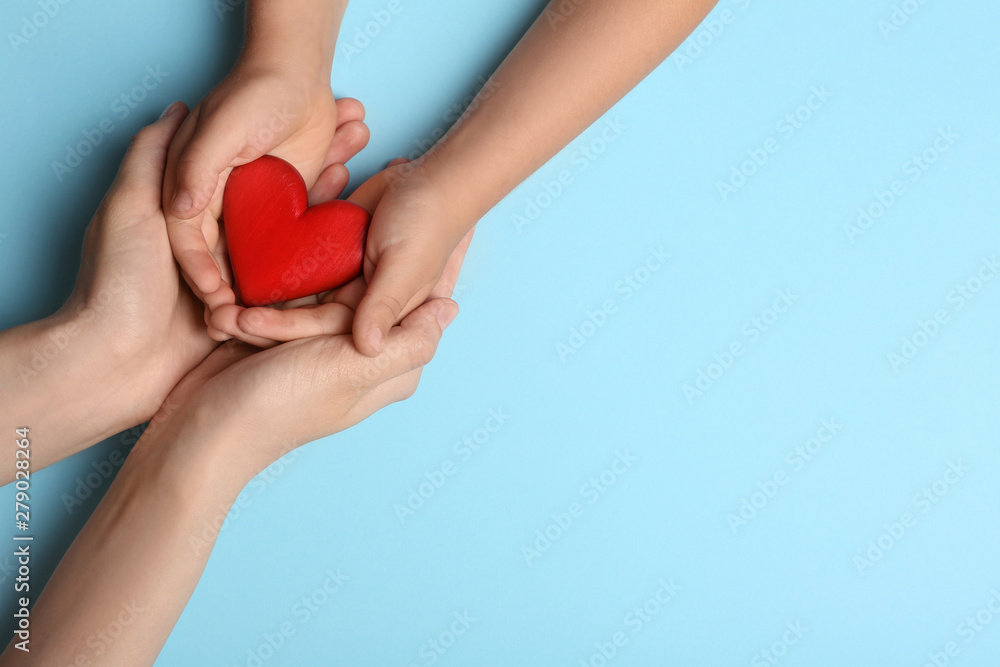 Fototapeta Woman and child holding heart on blue background, top view with space for text. Donation concept