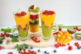 Fototapeta Fototapety do kuchni -  Kolorowe warstwowe smoothie z mango, kiwi, selera naciowego, malin, porzeczek, banana, jarmużu i kremu waniliowego