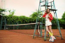 Happy Stylish Young Woman With Vintage Roller Skates And Headphones On Tennis Court. Space For Text