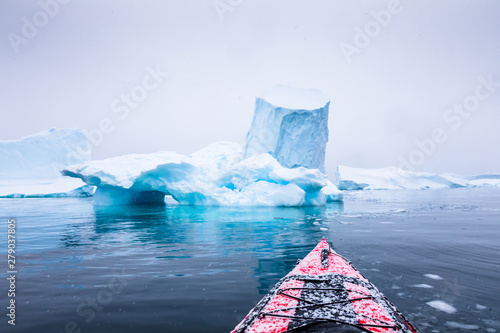 Fotobehang Antarctica Kayaking between icebergs on a red kayak in Antarctica, POV (point of view) photo with frozen white landscape and blue ice, amazing scene in Antarctic Peninsula, extreme activity