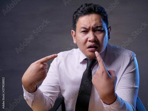 Photo Asian Businessman Pointing Himself with Unhappy Expression as if he confused to