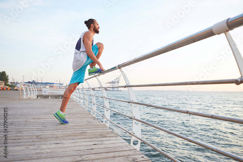 Portrait of young attractive bearded guy doing stretching for legs, morning exercises by the sea, warm-up after run, leads healthy active lifestyle Fototapet