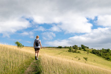 Woman Hiking On A Field On The Cotswold Way, Gloucestershire, England