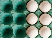 White Eggs Arranged Together To The Right Side Of A Green Egg Carton With Empty Spaces On The Left Side.