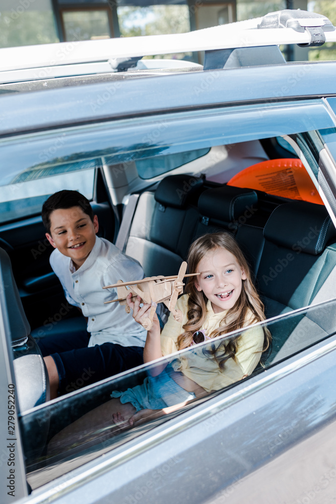 Fototapety, obrazy: overhead view of happy kid holding wooden biplane near brother in car