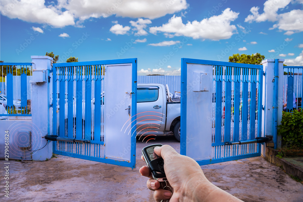 Fototapeta Man used hand remote control to open swing gate door by motor automation is home security system with blue cloud sky background.