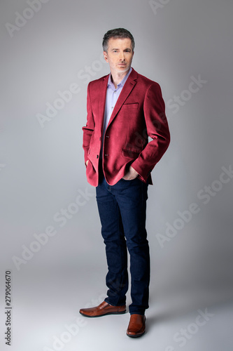 Middle-aged Caucasian businessman looking posh wearing modern fall collection style maroon or red jacket.  Depicts confident and mature stylish fashion.  Shot in studio for catalog look.