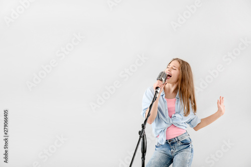Teenage girl with microphone singing against light background - 279066405