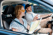 selective focus of woman in sunglasses pointing with finger while holding map in car near man