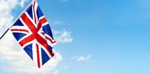 United Kingdom Flag Waving On Wind In Blue Sky
