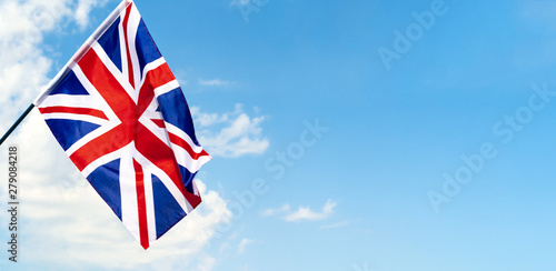 United Kingdom Flag waving on wind in blue sky Canvas Print