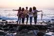 canvas print picture - Love and friendship concept with group of female people enjoying the sunset on the ocean together -