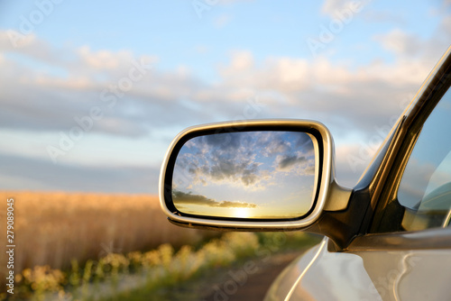 Sunset sky reflect in rearview mirror of car.