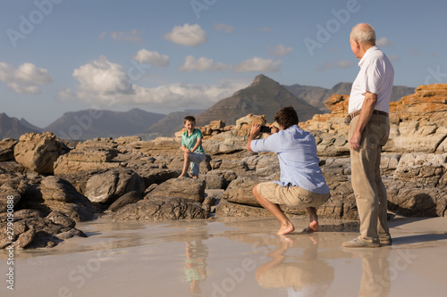Father clicking photo of his son with mobile phone on beach
