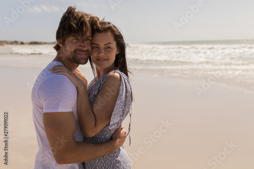 Romantic happy young couple embracing on beach
