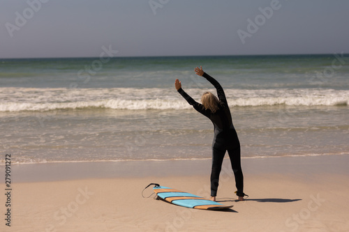 Rear view senior female surfer with surfboard exercising on the beach