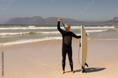 Side view of senior male surfer standing with surfboard on the beach