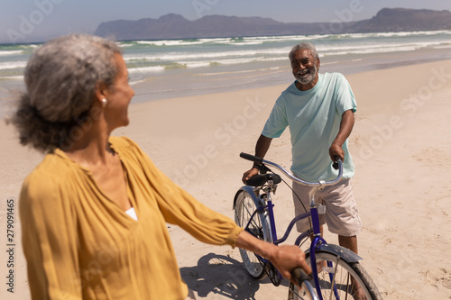 Senior couple standing with bicycle and looking each other on beach with mountains in the back