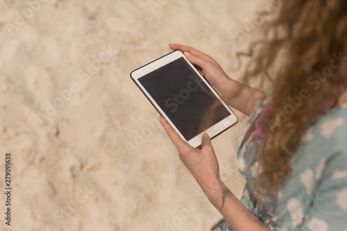 Young Caucasian woman using digital table on beach