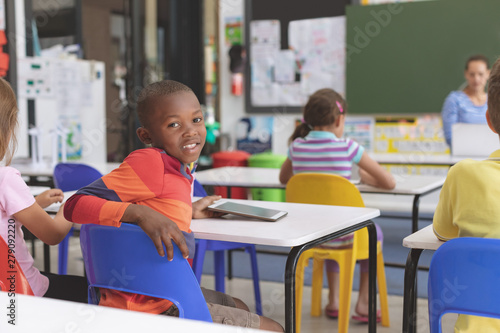 Happy schoolboy looking at the camera and holding digital tablet at desk in classroom