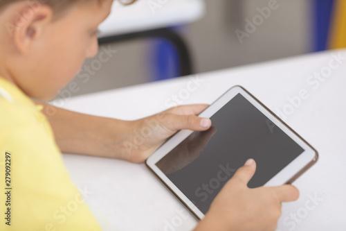 Schoolboy using digital tablet at desk in classroom