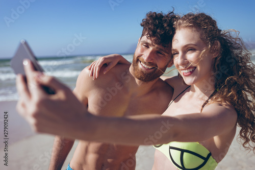 Couple taking selfie standing at beach