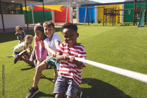 Fotografie, Tablou Group of school kids playing tug of war