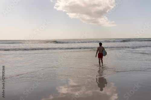 Young male surfer with surfboard walking on beach