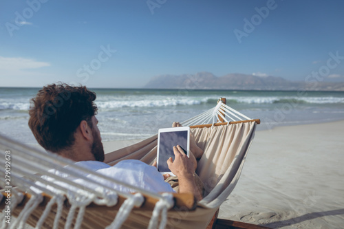 Man using digital tablet while lying on hammock at beach  - fototapety na wymiar