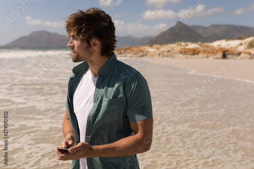 Young man looking away while using mobile phone on beach