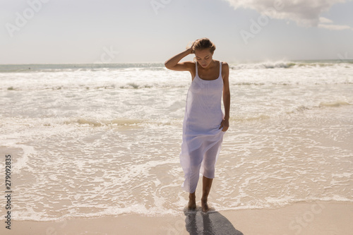 Young woman with hand on head standing at beach